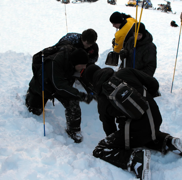 Three avalanche rescuers shovelling in an improper cone shape.