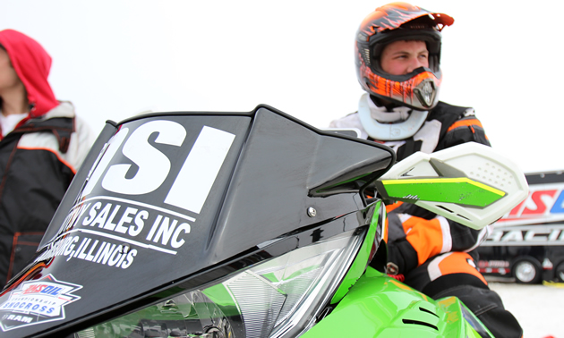 Grant Glashagel snocross racer sitting on his green sled.