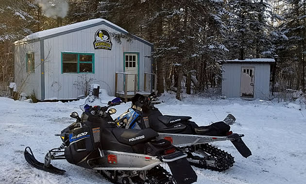 Two sleds parked outside a warm up shelters near Powerview-Pine Falls.