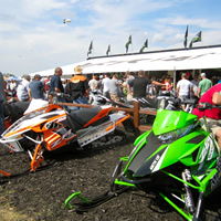 People milling around a green arctic cat and an orange and white arctic cat.
