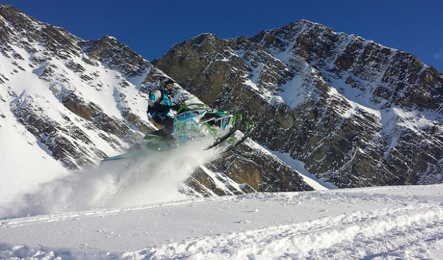 Heather White catching some air on her sled.  She has a range of mountains showing in the near background.