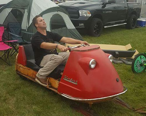 John Samolis sitting on his Herters snowmobile before it was restored.