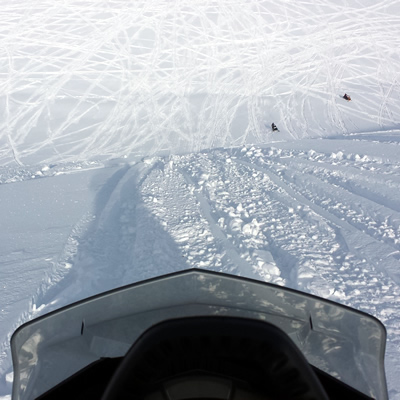 Looking over the handlebars at a steep climb on a snowmobile.