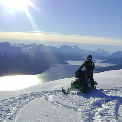 A snowmobiler in the sun on the top of a mountain.