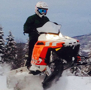 A snowmobiler on an orange and white sled getting some air.