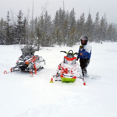 Three sleds and two riders stopped on the snowy trails in Hudson Bay.