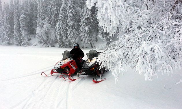 A woman sitting on a snowmobile.