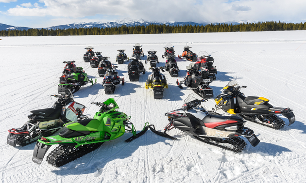 sledders gathered in a circle on their snowmobiles