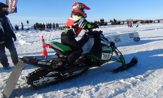A young woman sitting on a snowmobile at the snow drags.