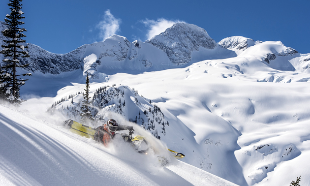 Jeremy Hanke carves a line with stunning mountain terrain in the background.