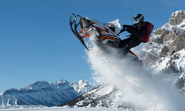 A man soaring through the air on a white sled.