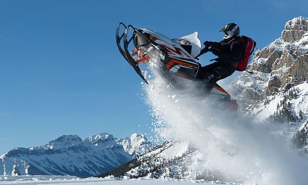 A man soaring through the air on a white sled.