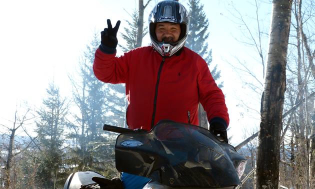 A man from Mexico giving the peace sign on a snowmobile.
