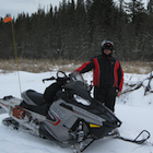 Man standing beside a snowmobile and a beaver lodge.