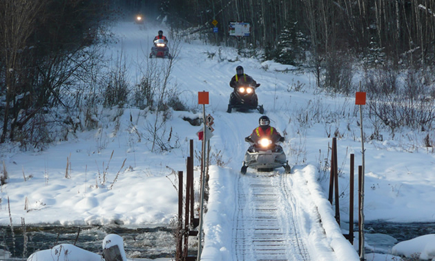 Two sledders about to ride over a bridge.