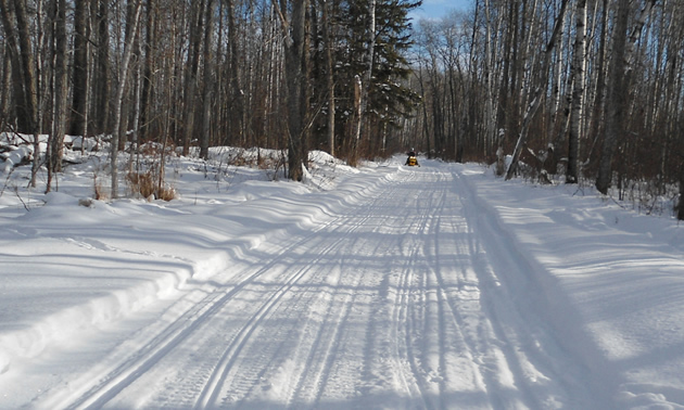 A snowmobiler riding down a long, smooth trail.