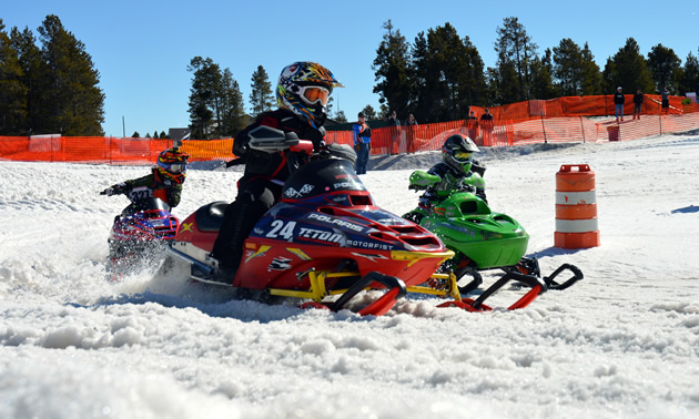 Kids racing snocross on 120-cc snowmobiles in West Yellowstone.