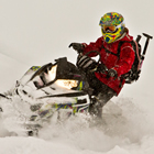 A woman in red jacket on a black snowmobile.