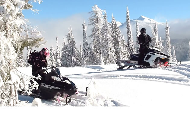 A woman in a pink helmet on a black snowmobile in the backcountry.