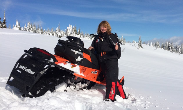A woman by a Ski-Doo snowmobile in the backcountry.