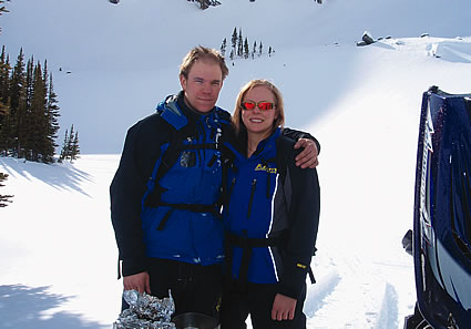 man and woman standing in the snow in snowmobiling suits