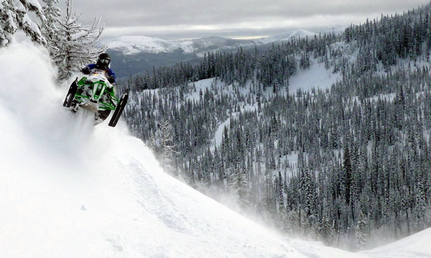Snowmobiler on a green arctic cat in Cranbrook.