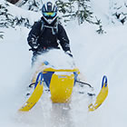 A person in black helmet and jacket on a blue and yellow Ski-Doo snowmobile.