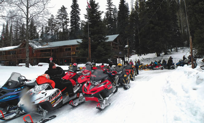 snowmobiles lined up in front of a log building