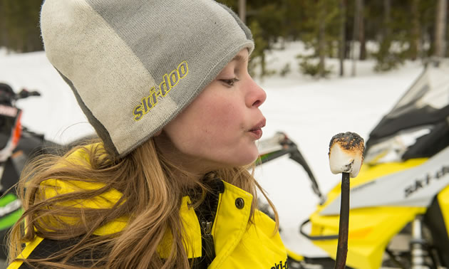 Girl, dressed in toque and winter coat, eating a roasted marshmallow.
