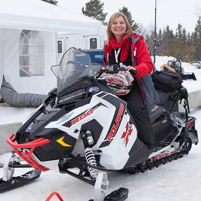 Maryann Chichak on a red and white Polaris snowmobile.