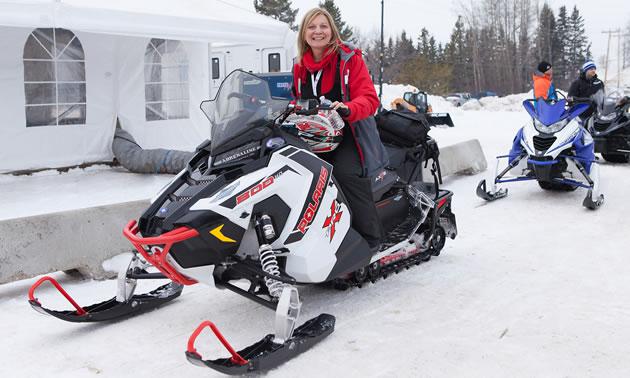 Maryann Chichak on a red and white Polaris snowmobile.