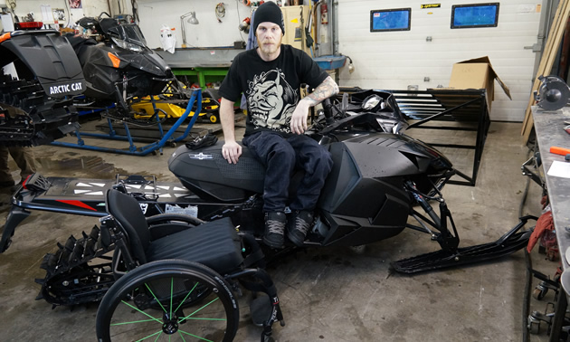 A young man sitting on a black sled with his wheelchair beside him.