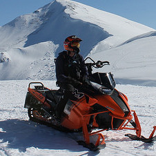 A sledder sitting on his snowmobile.