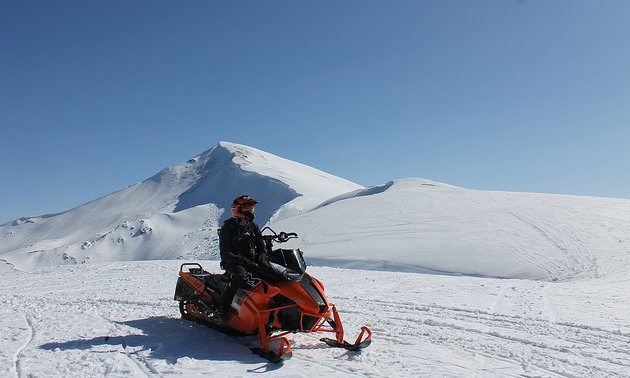 A sledder stopped with two mountain peaks in the background.