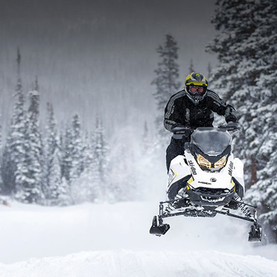 Picture of snowmobiler riding along snowy trail.