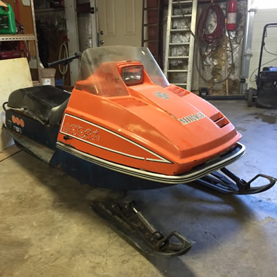 An orange Mirage snowmobile sitting inside of a garage.
