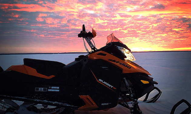 A Ski-Doo sled parked on a lake with the pink sunset behind it.