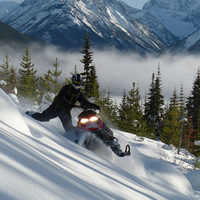 A man sidehilling on a red Rev snowmobile.