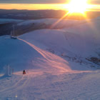 Photo of a person riding a snowmobile along a ridge with the sunset in the foreground.