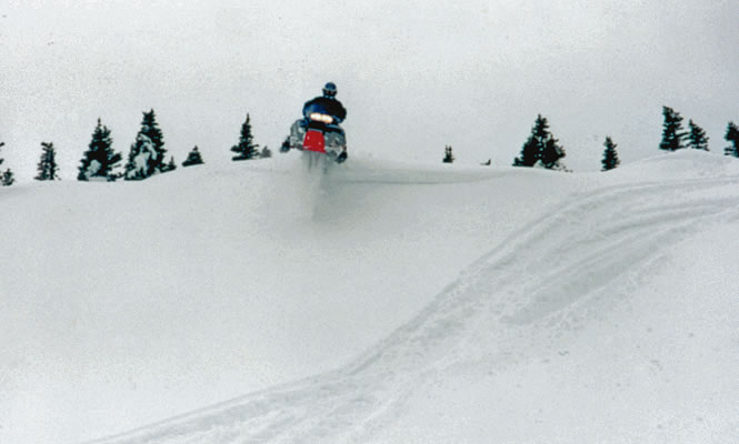 a snowmobiler taking a jump over a hill