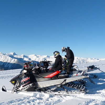 Mountain snowmobilers sitting on top of a mountain on a bluebird day.