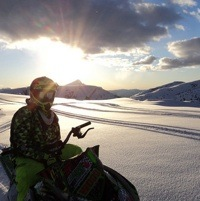 Nadine Overwater sitting on her sled enjoying the view of the sun going down over the snowcovered mountains.