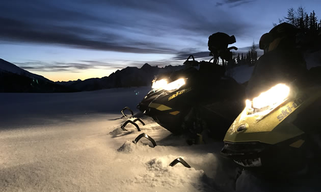 Three Ski-Doo's lined up on top of the mountain.