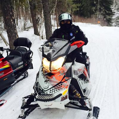 A picture of Derek Silversides, enjoying his first snowmobile ride.