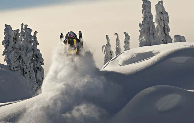 A shot of the back of a snowmobiler as he's going over a windlip.