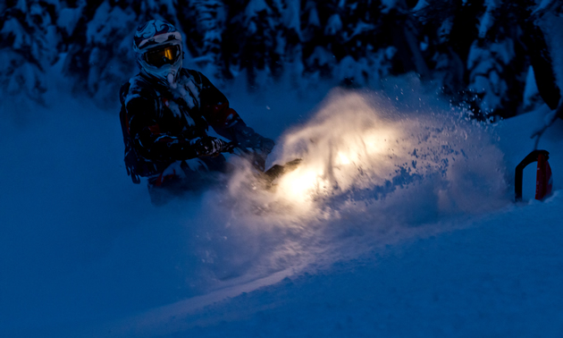A snowmobiler riding in the dark.