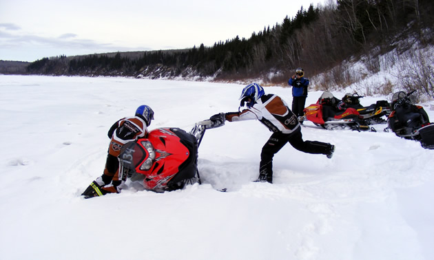 Snowmobilers trying to get a tipped over sled upright.