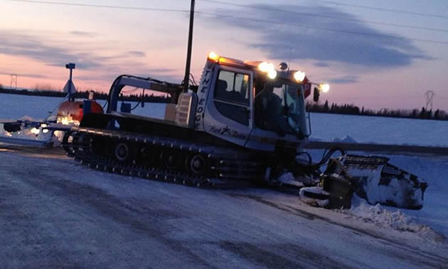 A snowmobile trail grooming machine with a drag behind it.