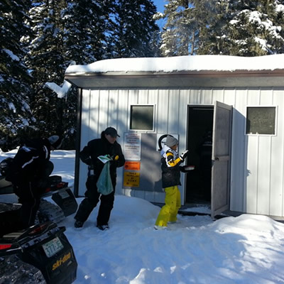 A group of snowmobilers standing by their sleds near a warm up shelter.