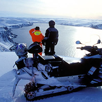 Snowmobilers looking down at a fjord in Norway.